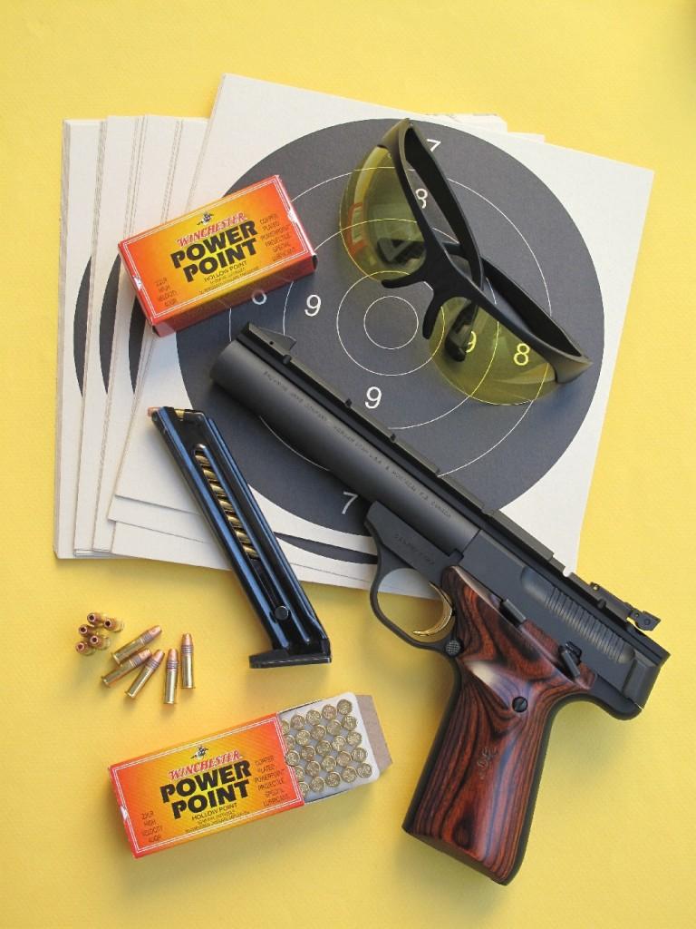 Le pistolet Browning Buck Mark Field reçoit une très belle finition satinée noire mate sur laquelle tanche ses plaquettes de crosse en bois exotique et sa queue de détente dorée. Il est ici accompagné par des cartouches à balle expansive Power Point, manufacturées par la firme américaine Winchester.