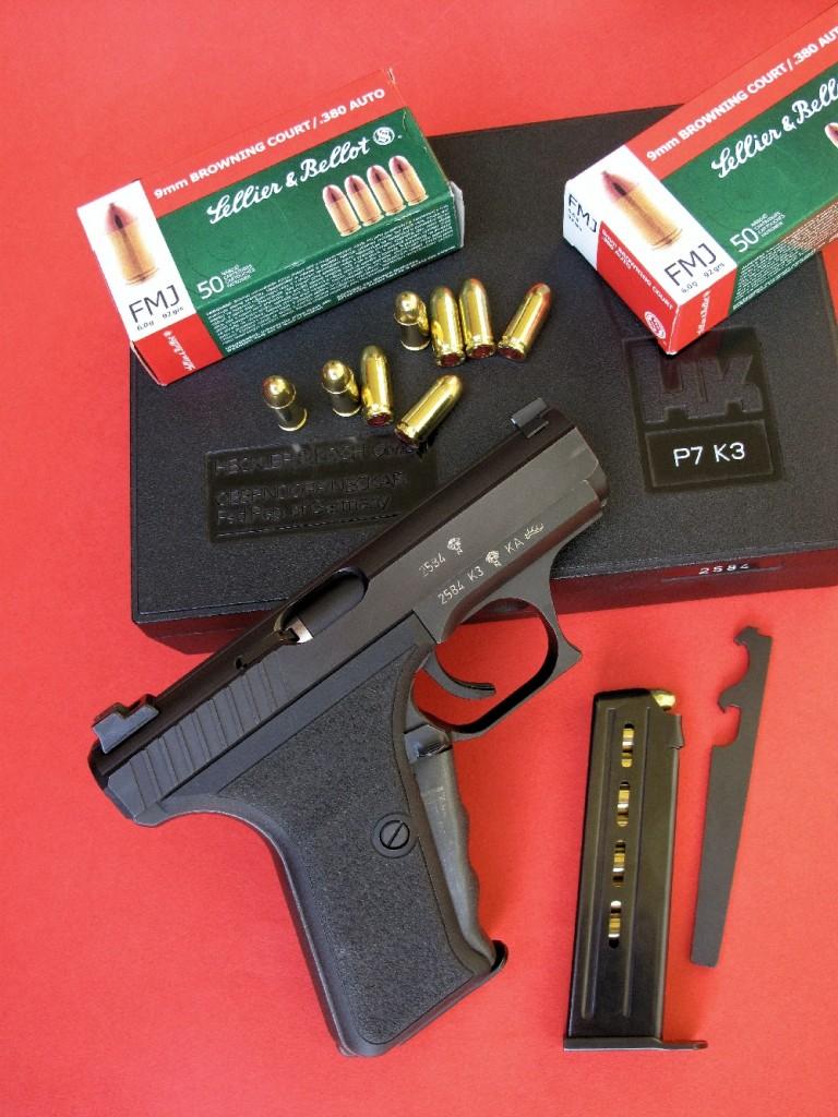 La présence de la pédale d'armement, à l'avant de la poignée, procure au HK P7 K3 sa silhouette très caractéristique. Ce pistolet est accompagné ici par sa boîte d'origine, son chargeur de rechange et l'outil spécial permettant le démontage du canon et du percuteur.