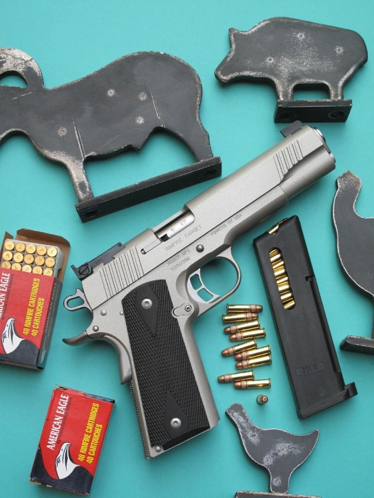 Le Kimber Rimfire Target « Silver », qui reprend avec une grande exactitude l'aspect et les dimensions du Colt 1911 A1, se démarque par sa finition chromée satinée et par ses plaquettes en néoprène. Pour les besoins de la photo, il est accompagné ici des mini-silhouettes métalliques destinées aux armes d'épaule de calibre 22 Long Rifle, plus petites celles dédiées aux armes de poing de même calibre.