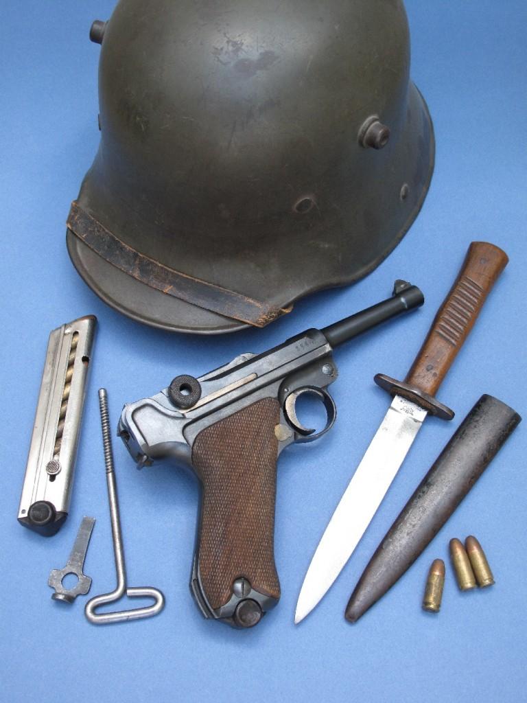 Pistolet semi-automatique allemand Luger P-08 (modèle 1908) de la Première Guerre mondiale, fabriqué par la DWM (Deutsche Waffen und Munitionsfabriken) en 1916, calibre 9 mm ParabellumIl est ici accompagné d'accessoires d'époque : baguette de nettoyage, outil à usage multiple (tournevis et aide au remplissage du chargeur), casque et poignard de tranchée allemands de la Grande Guerre.
