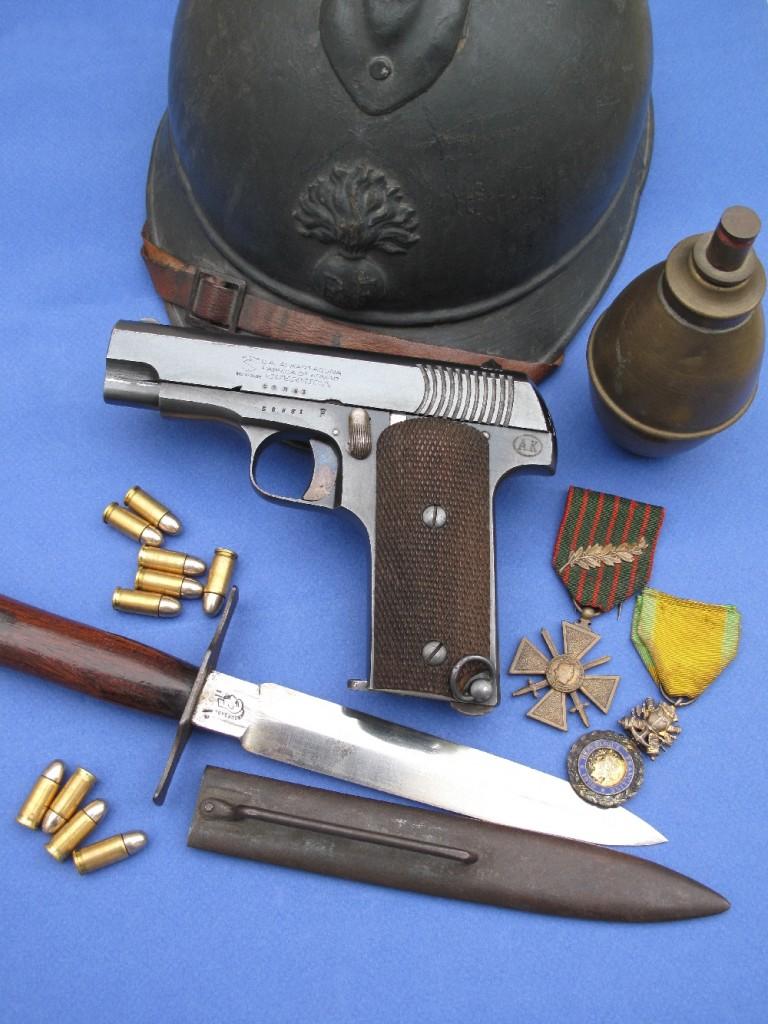 Le pistolet Alkar type Ruby 14-18 dans son environnement historique de la « Grande Guerre » : casque Adrian modèle 1915, grenade « citron » suffocante (éther bromacétique) avec allumeur à friction, poignard de tranchée modèle 1916, fabriqué à Thiers par la maison Bourgade aîné (poinçon « tête de chinois »), croix de guerre et médaille militaire.