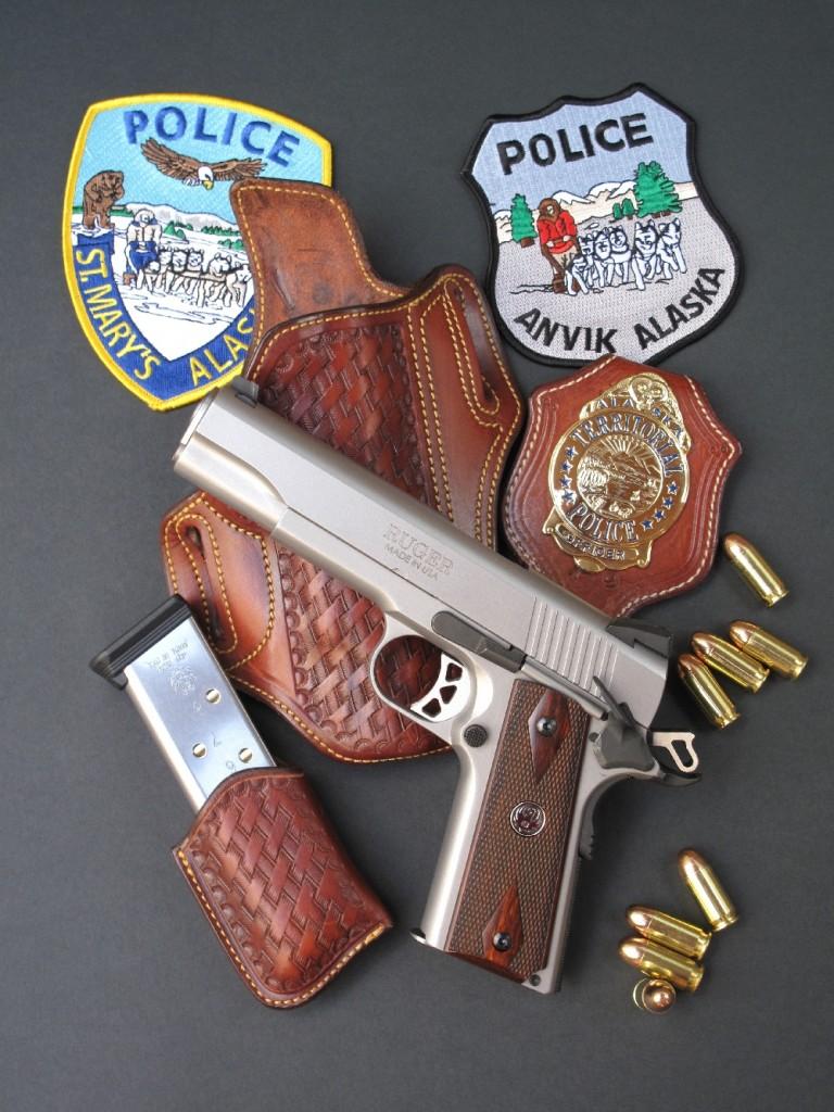 Le pistolet Ruger modèle SR1911, accompagné d'écussons brodés (patches) de la police en Alaska et d'un ensemble en cuir« basket », composé d'un holster, d'un porte-chargeur et d'un porte insigne (badge), réalisé par la maison française La sellerie du Thymerais.