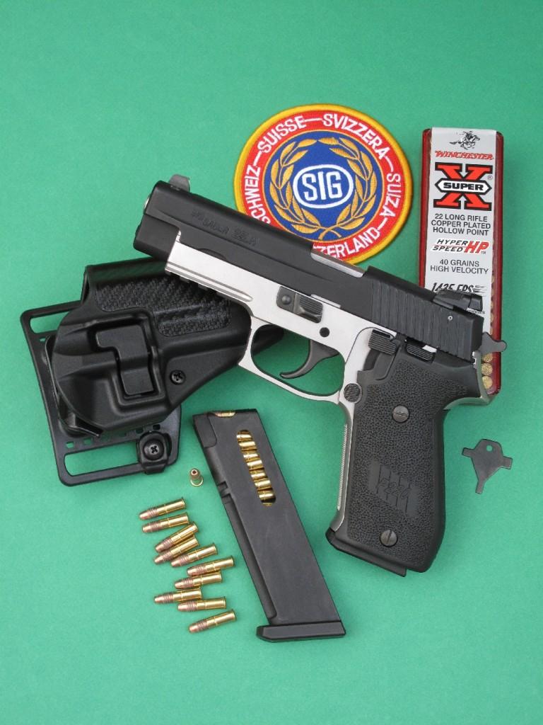Le pistolet semi-automatique SIG P220-22 est une arme de grande qualité… malheureusement desservie par un chargeur de dix coups en matière plastique qui n'est absolument pas à la hauteur ! Le pistolet est ici accompagné par son chargeur de rechange, l'outil permettant le réglage de la hausse et un holster à rétention « Serpa Concealment », moulé en polymère avec décor en fibre de carbone, fabriqué aux USA par la maison Blackhawk.