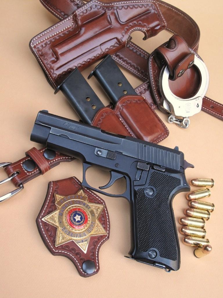 Le SIG-Sauer P220, présenté dans le contexte des forces de l'ordre aux USA, avec un badge de deputy (sheriff adjoint) de l'état du Texas, deux chargeurs de secours et une paire de menottes Smith & Wesson, dans un ensemble en cuir réalisé par la maison française La Sellerie du Thymerais.