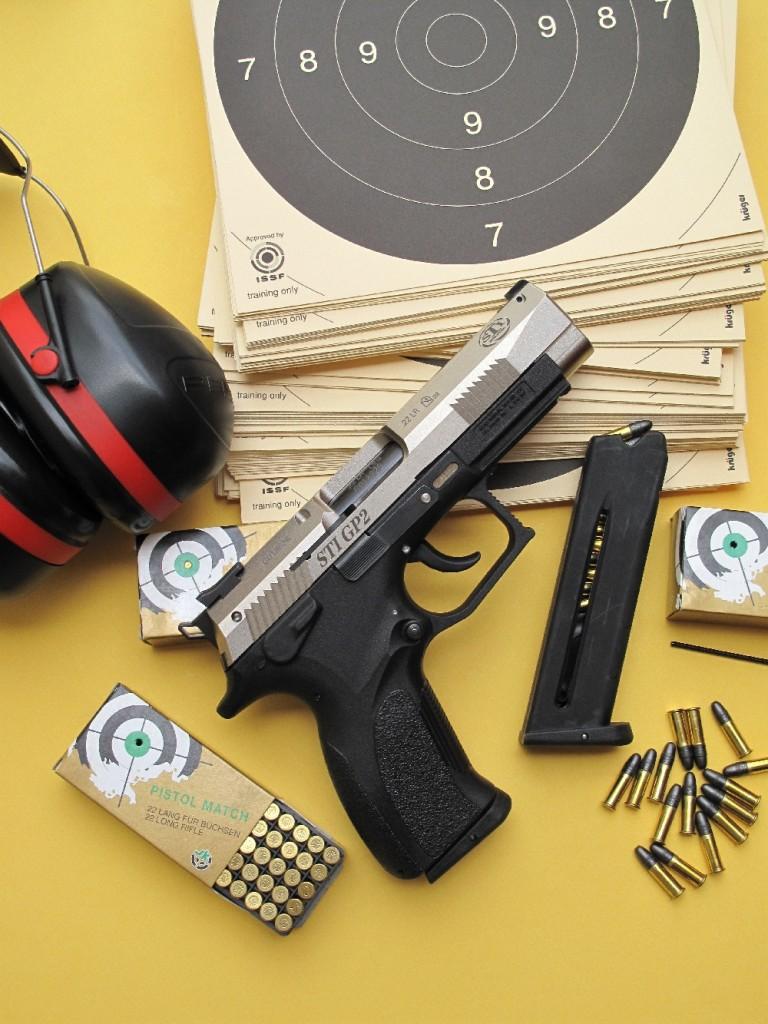 Le pistolet GP2 de la firme américaine STI, qui correspond au modèle K22 de la manufacture slovaque Grand Power, accompagné par son chargeur de rechange d'une contenance de 14 coups et par des munitions Pistol Match encartouchées par la maison allemande SK (aujourd'hui absorbée par la manufacture finlandaise Lapua).