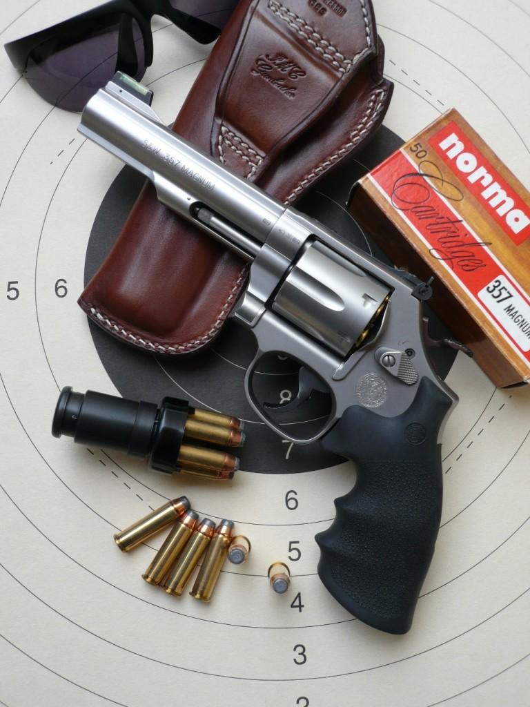 Le revolver Smith & Wesson 686 French Target 2 est livré dans une élégante mallette de transport en aluminium, avec deux poignées interchangeables (Hogue en néoprène et Karl Nill en noyer) et un rail porte-accessoires tactiques amovible. Il est ici accompagné d'un holster en cuir réalisé par le sellier français Jean-Marie Chardin, d'un Speedloader COMP III et d'une boîte de cartouches Norma à balle 158 grains Soft Point Flat Nose