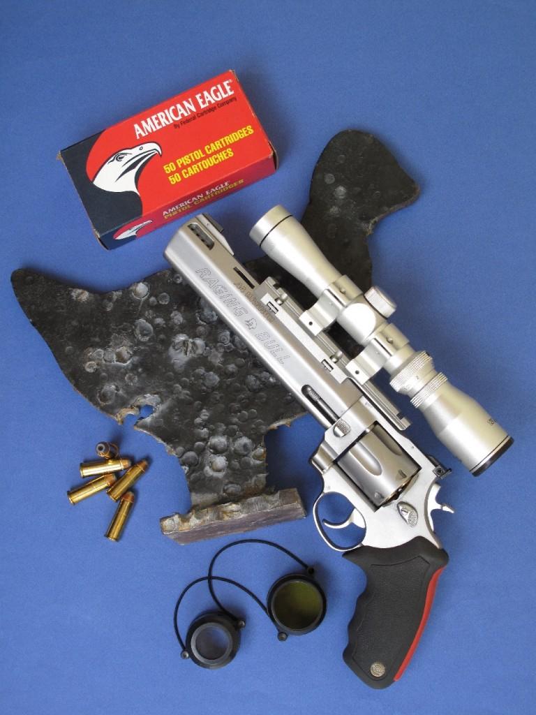 Le Taurus modèle 444 Raging Bull se présente comme un revolver de gros calibre bénéficiant d'une robuste construction en acier inoxydable massif. On remarquera la présence d'un ingénieux cache en polymère qui permet de protéger sa hausse durant le transport. Equipé d'une lunette, il se révèle idéal pour la chasse (aux USA) et le tir sur silhouettes métalliques. Il est accompagné ici de la lourde silhouette en acier que l'on tire à la distance de 50 mètres.